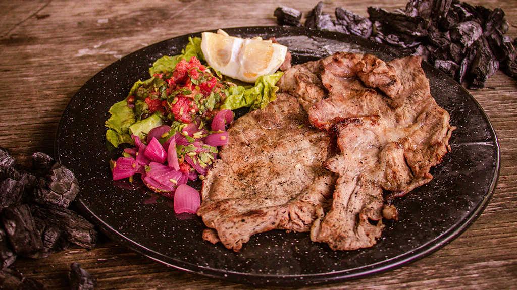 Poco Chuc preparado con filetes de puerco y achiote, platillo tradicional de Riviera Maya