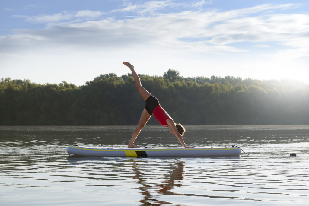 Practicing paddleboard yoga, a great idea to start the celebration of the 4th of July